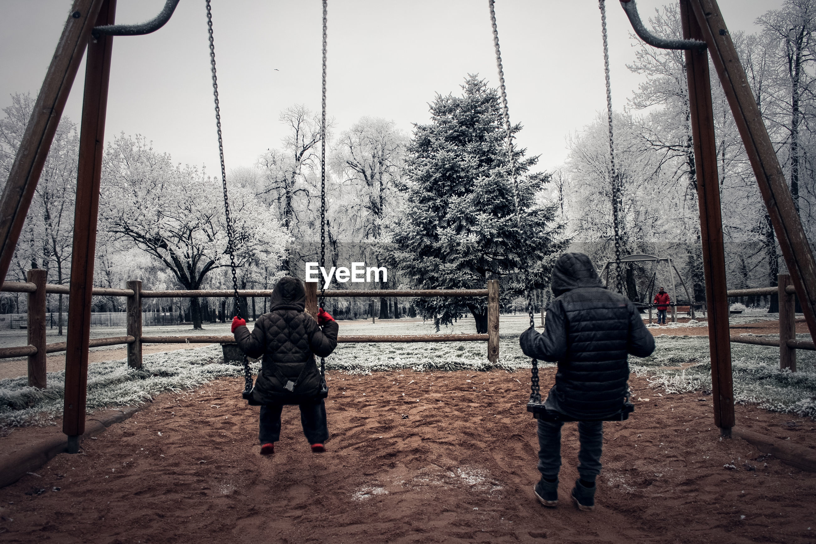Rear view of children playing on swing at park during winter