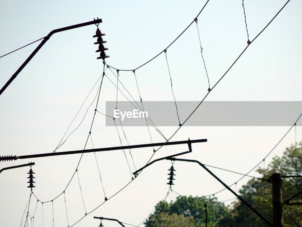 cable, sky, electricity, power line, low angle view, no people, technology, nature, connection, power supply, electricity pylon, day, focus on foreground, outdoors, fuel and power generation, tree, clear sky, plant, built structure, metal, complexity, telephone line