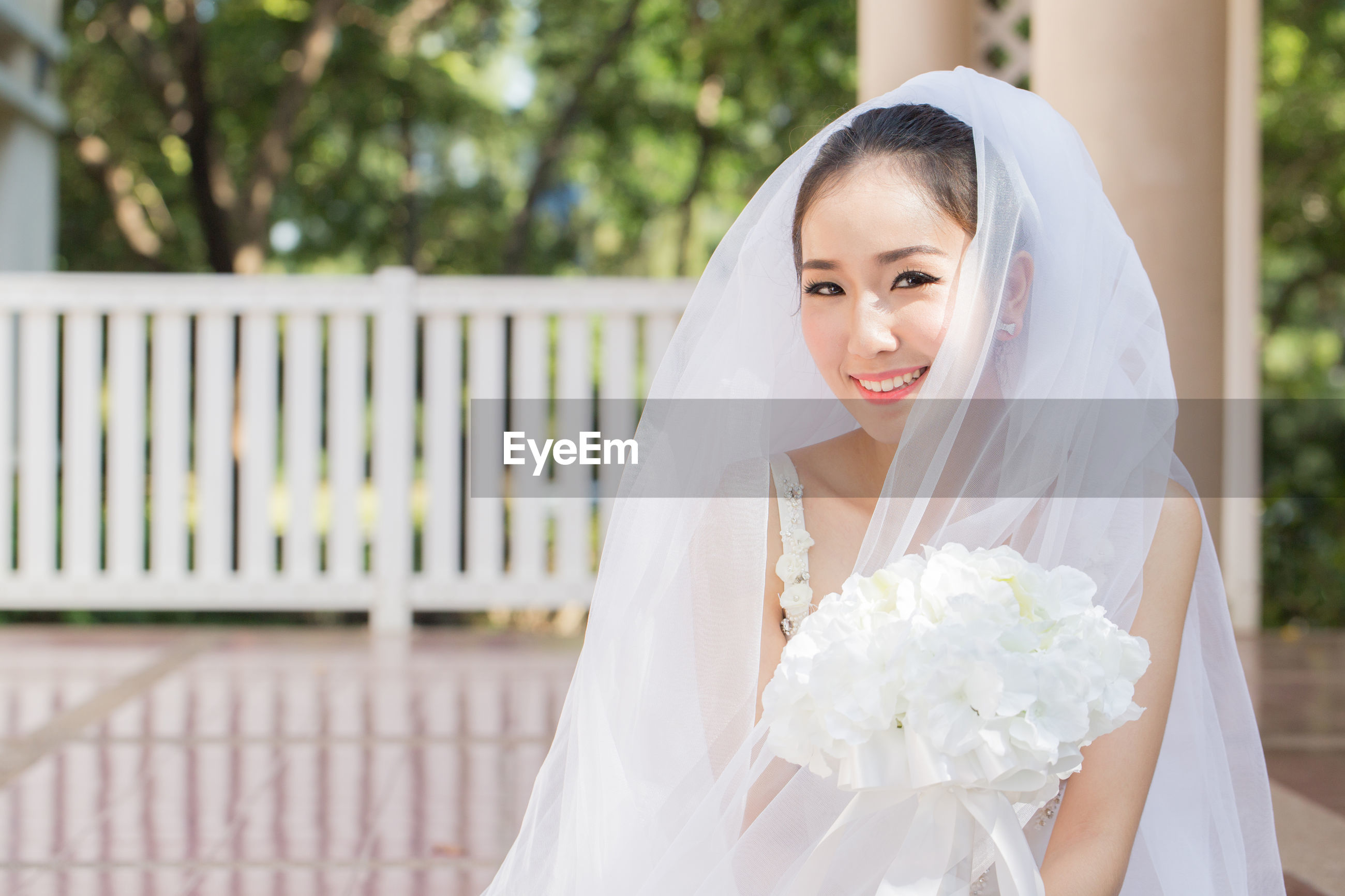 Portrait of smiling bride holding bouquet standing in park