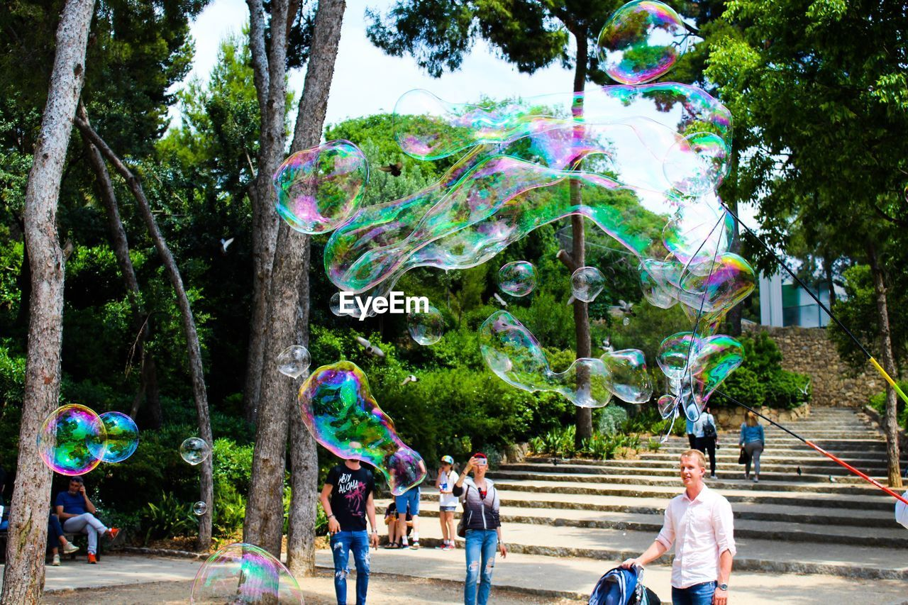 tree, bubble, real people, men, plant, leisure activity, nature, group of people, day, park, bubble wand, lifestyles, women, enjoyment, park - man made space, males, people, multi colored, fun, soap sud, outdoors