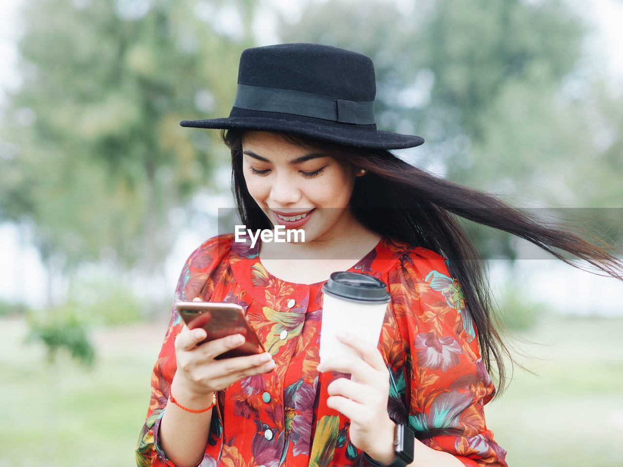 wireless technology, young adult, front view, real people, mobile phone, leisure activity, one person, clothing, hat, smiling, lifestyles, technology, holding, happiness, focus on foreground, young women, casual clothing, portable information device, connection, smart phone, outdoors, hairstyle, beautiful woman