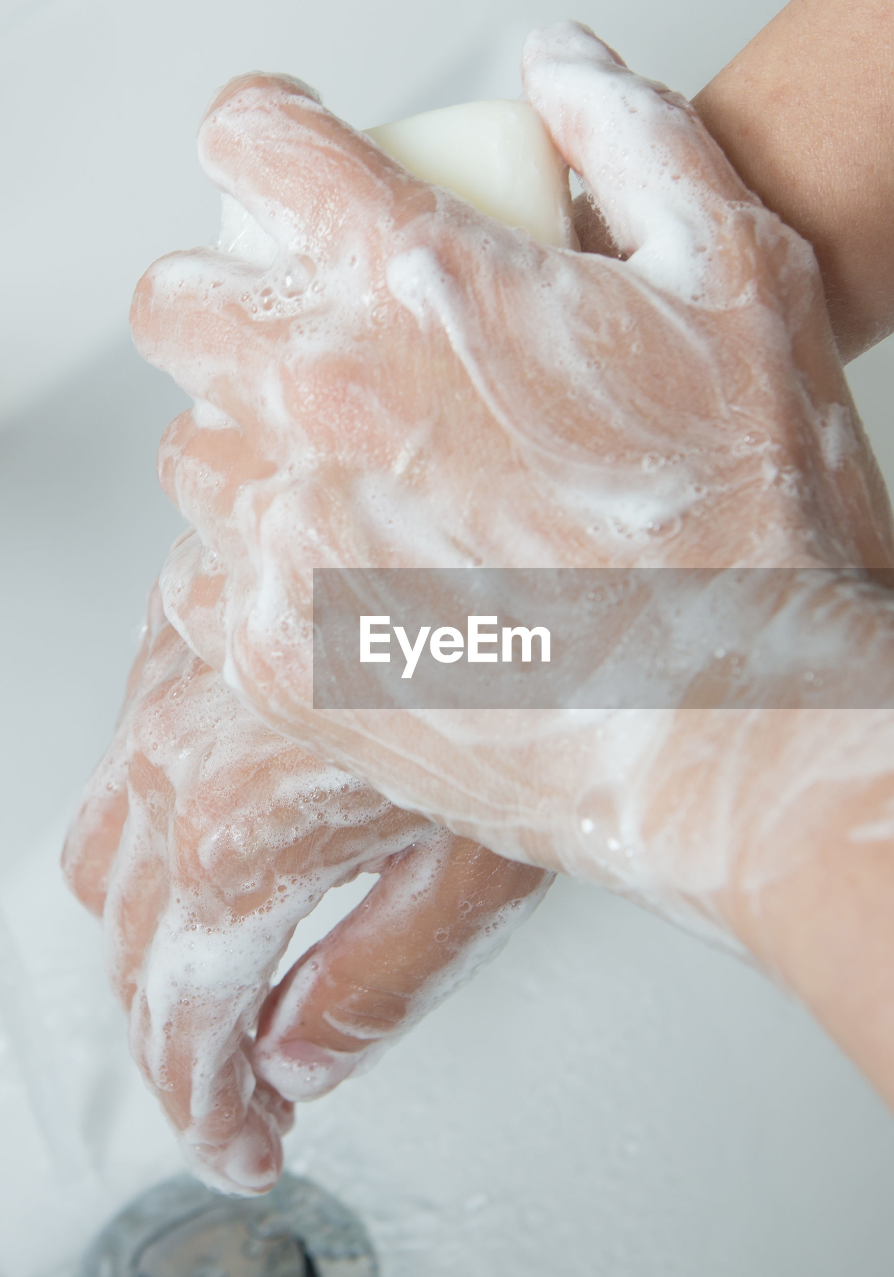 Cropped image of person washing hands in bathroom at home