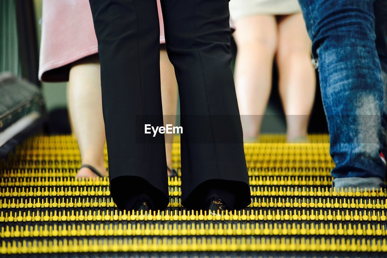Low Section Of People Standing On Escalator