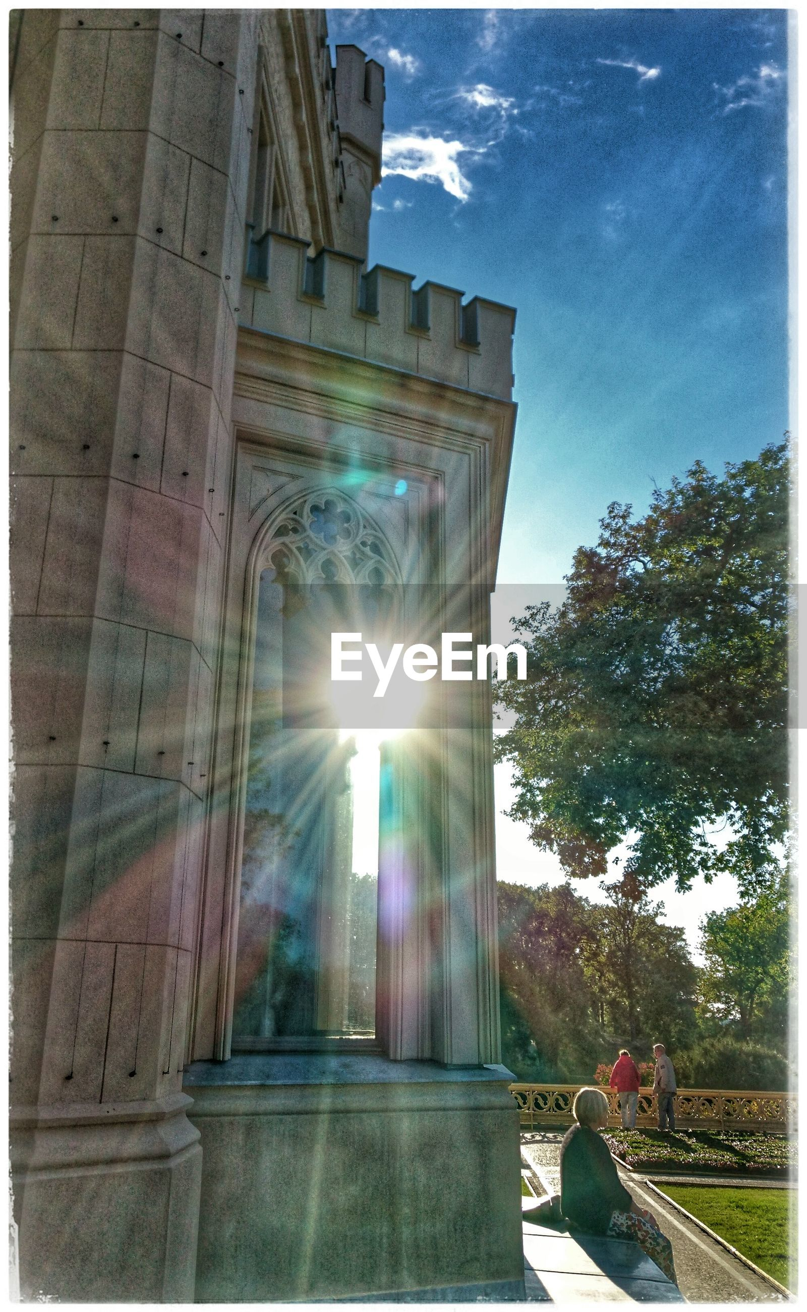 architecture, built structure, sunbeam, lens flare, low angle view, tree, building exterior, sky, sun, outdoors, growth, city life, day, blue, cloud - sky, bridge