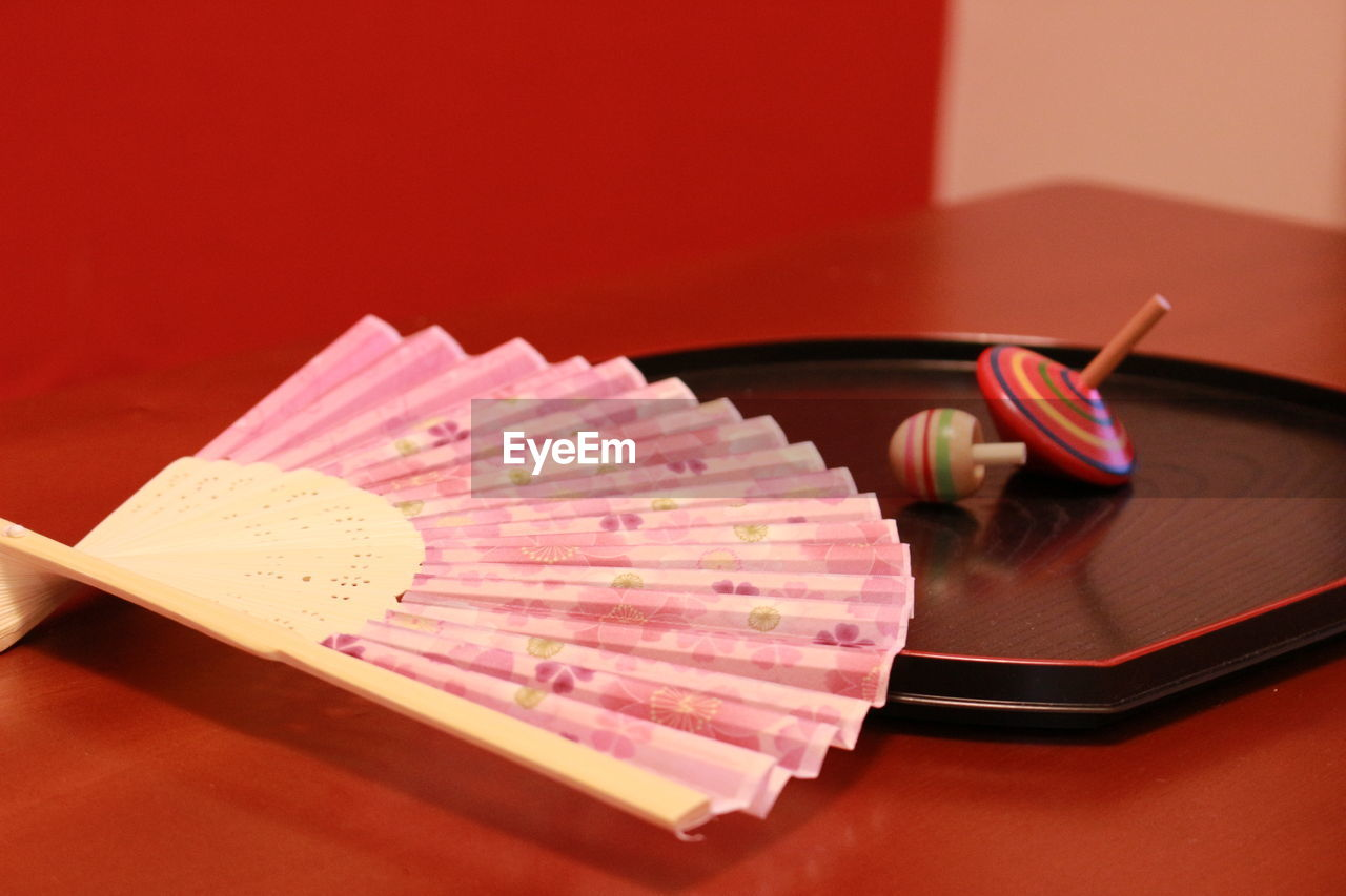 Close-up of pink folding fan with spinning tops on table