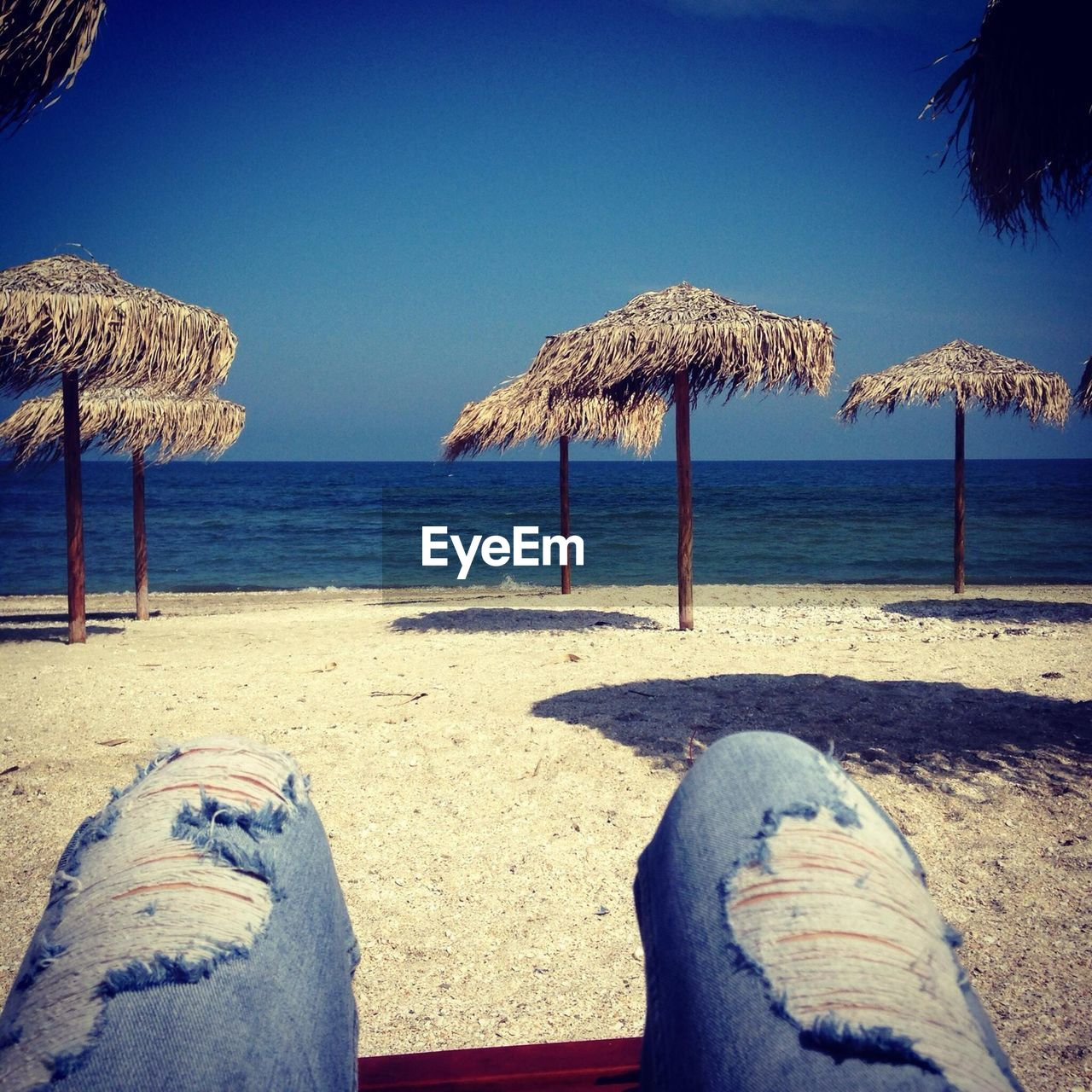 Midsection Of Person Wearing Torn Jeans While Sitting At Beach Against Clear Blue Sky