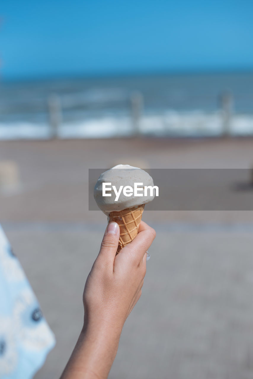 Cropped Hand Holding Ice Cream Cone At Beach