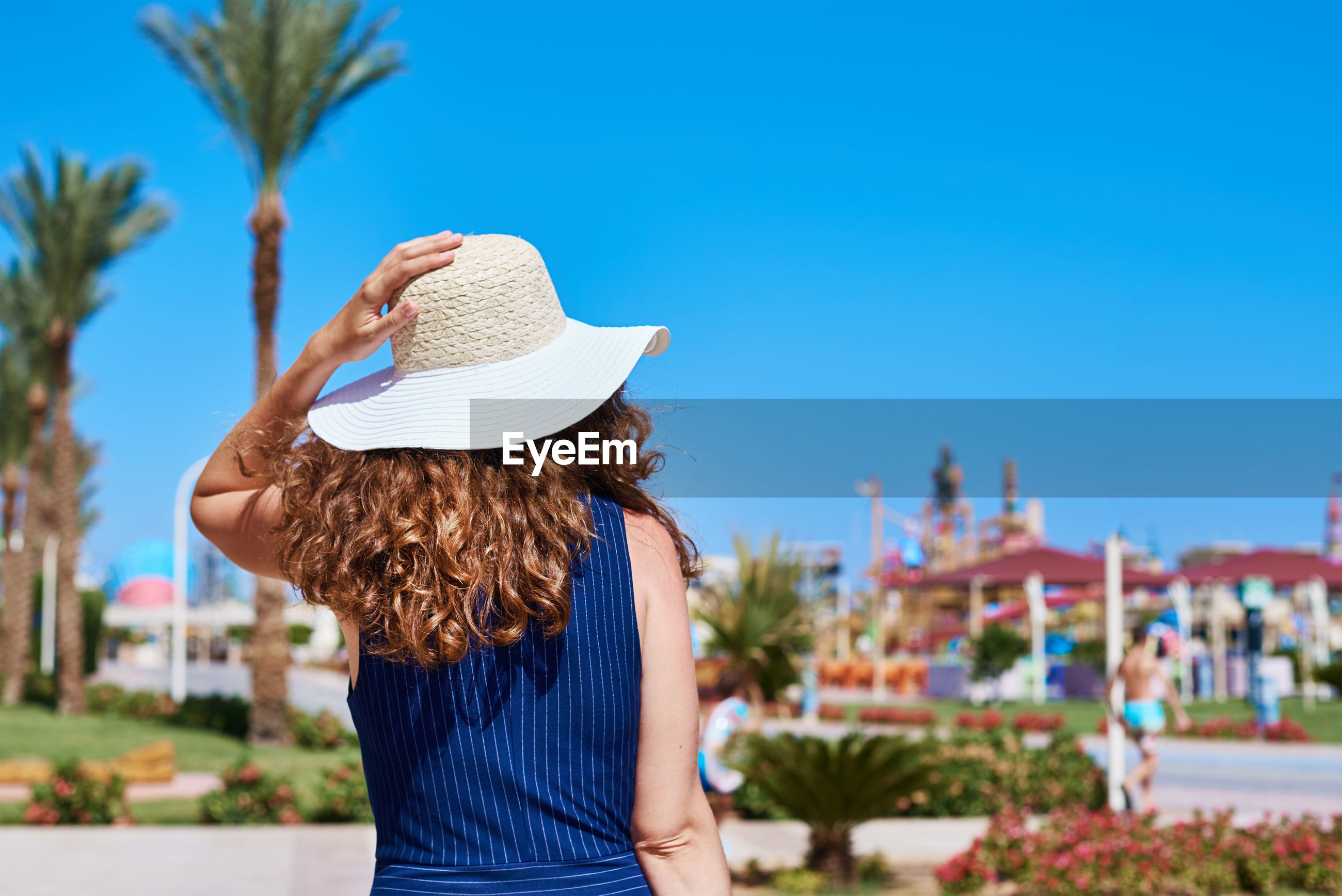Rear view of woman wearing hat against blue sky