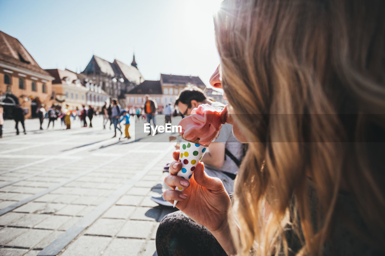 Woman Licking Ice Cream In City