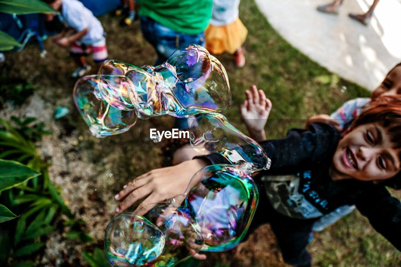bubble wand, bubble, fun, real people, holding, leisure activity, outdoors, fragility, high angle view, day, multi colored, childhood, cheerful, enjoyment, happiness, lifestyles, motion, togetherness, smiling, two people, low section, friendship, freshness