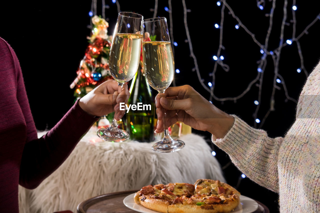 food and drink, real people, refreshment, human hand, holding, celebration, drink, hand, men, women, indoors, adult, food, alcohol, lifestyles, wine, glass, human body part, people, leisure activity, celebratory toast