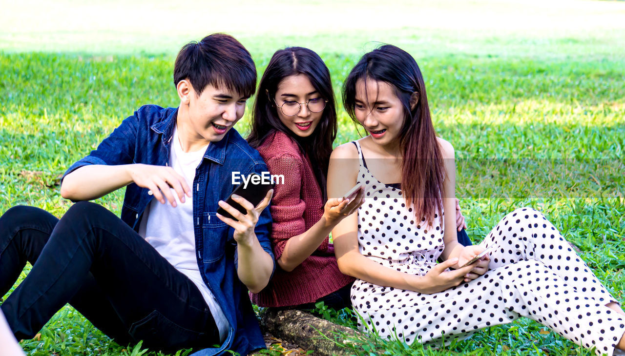Friends Using Mobile Phones While Sitting On Grassy Field At Park