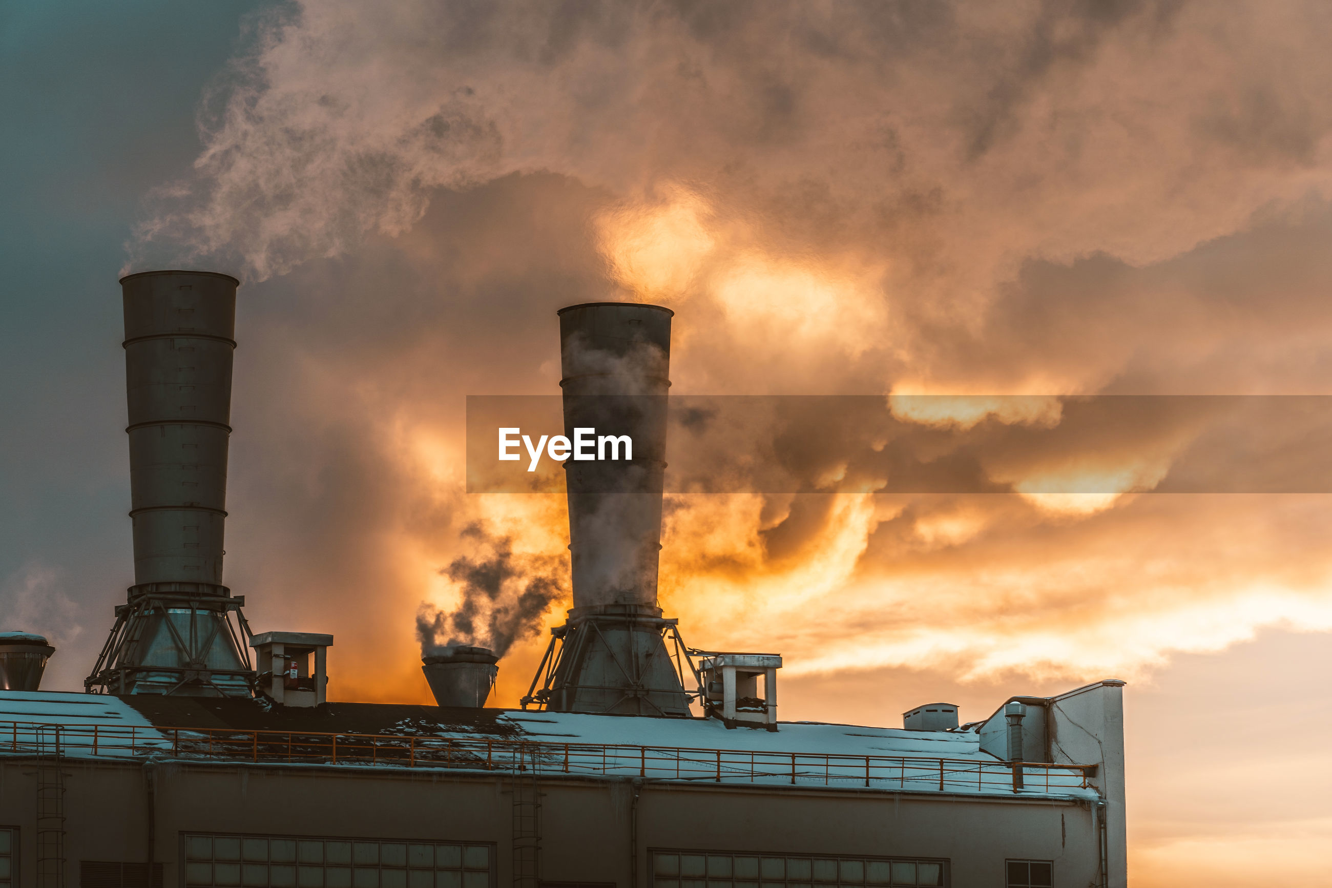 LOW ANGLE VIEW OF SMOKE STACKS AT SUNSET