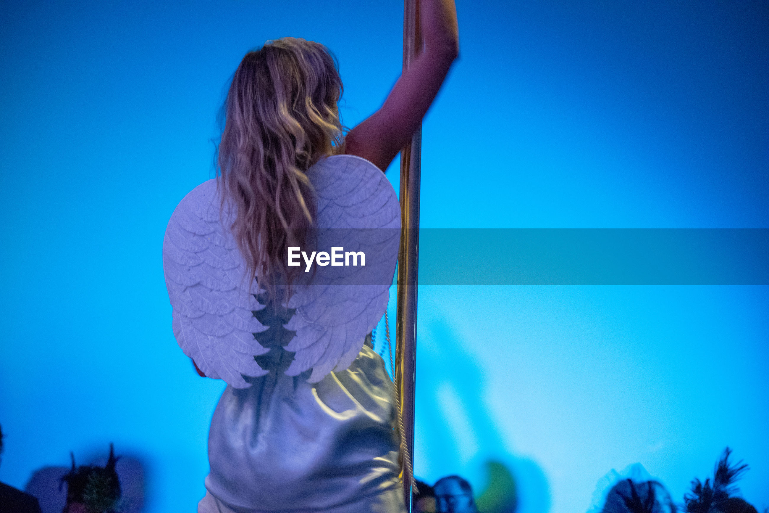 Rear view of woman pole dancing at nightclub