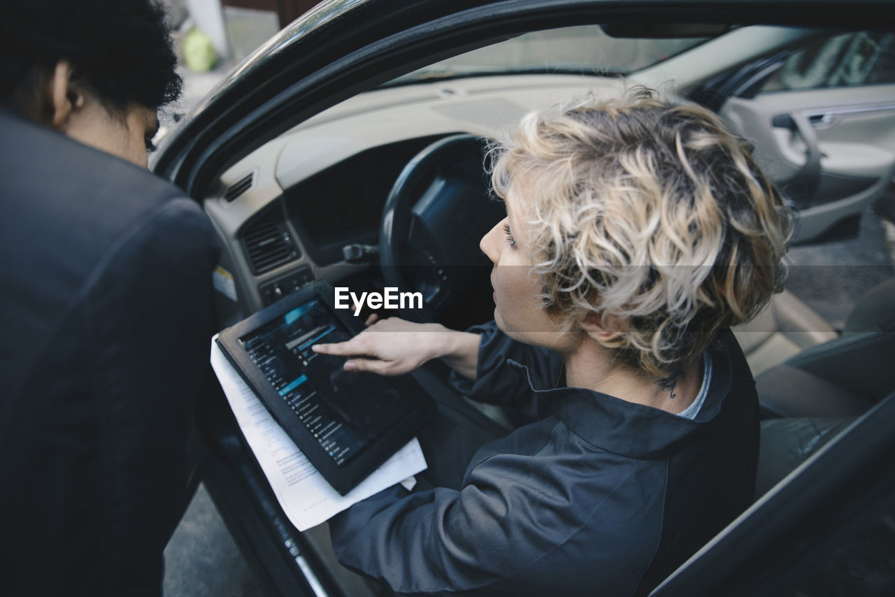 REAR VIEW OF WOMAN USING MOBILE PHONE WHILE CAR