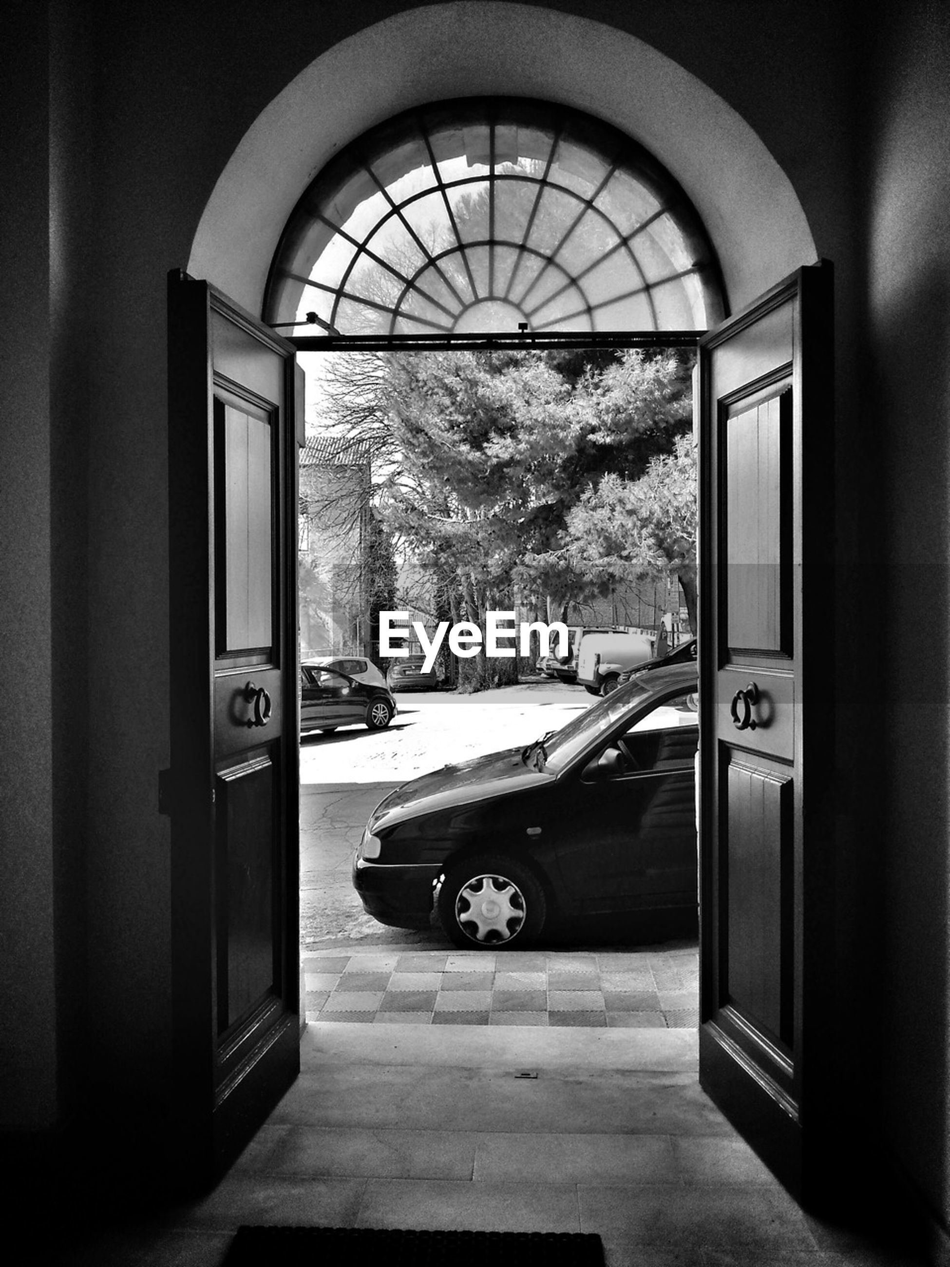 transportation, land vehicle, mode of transport, car, architecture, door, built structure, window, entrance, street, road, indoors, stationary, building exterior, arch, tree, house, day, parking, incidental people