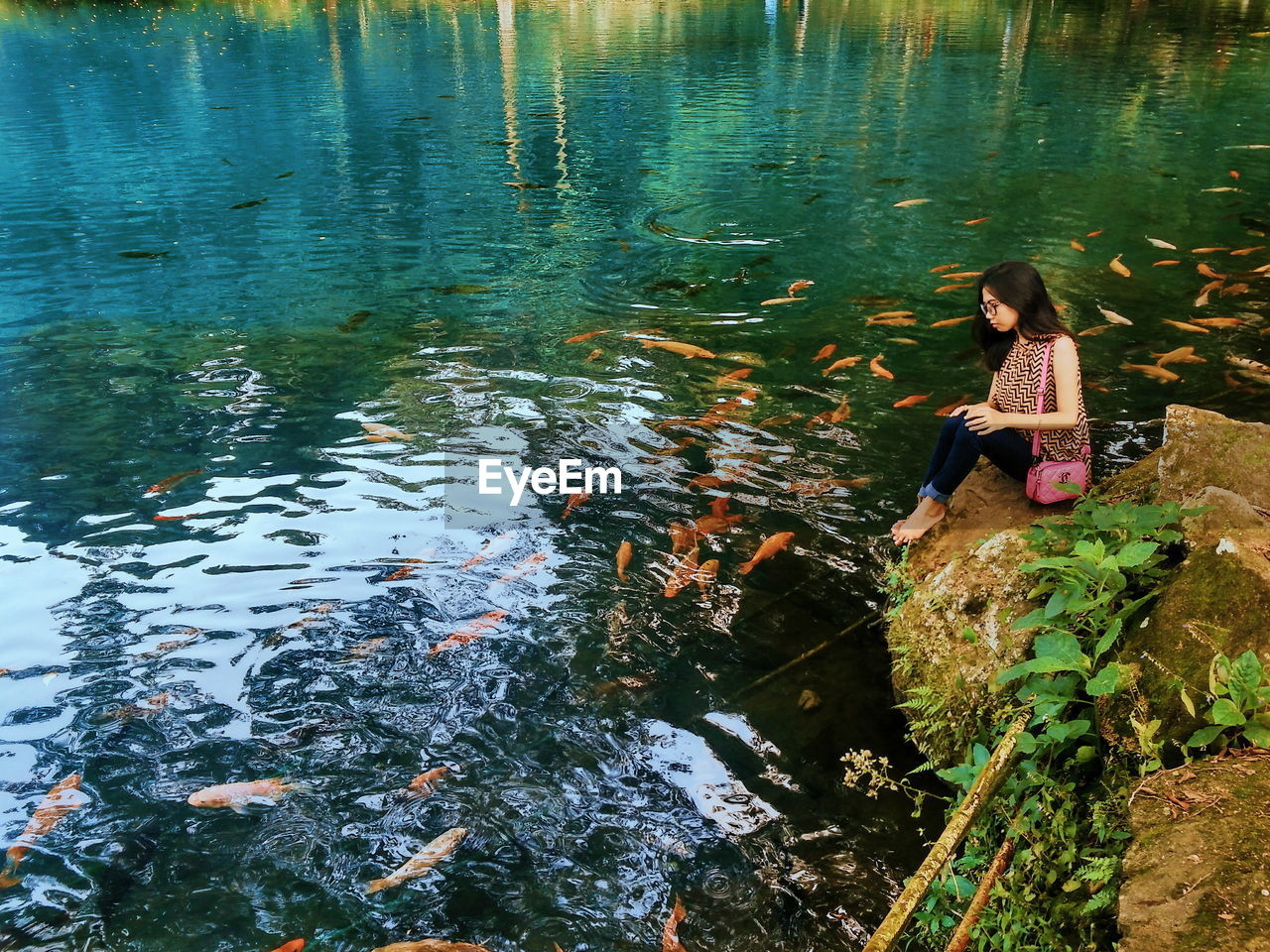Woman looking at fishes in lake