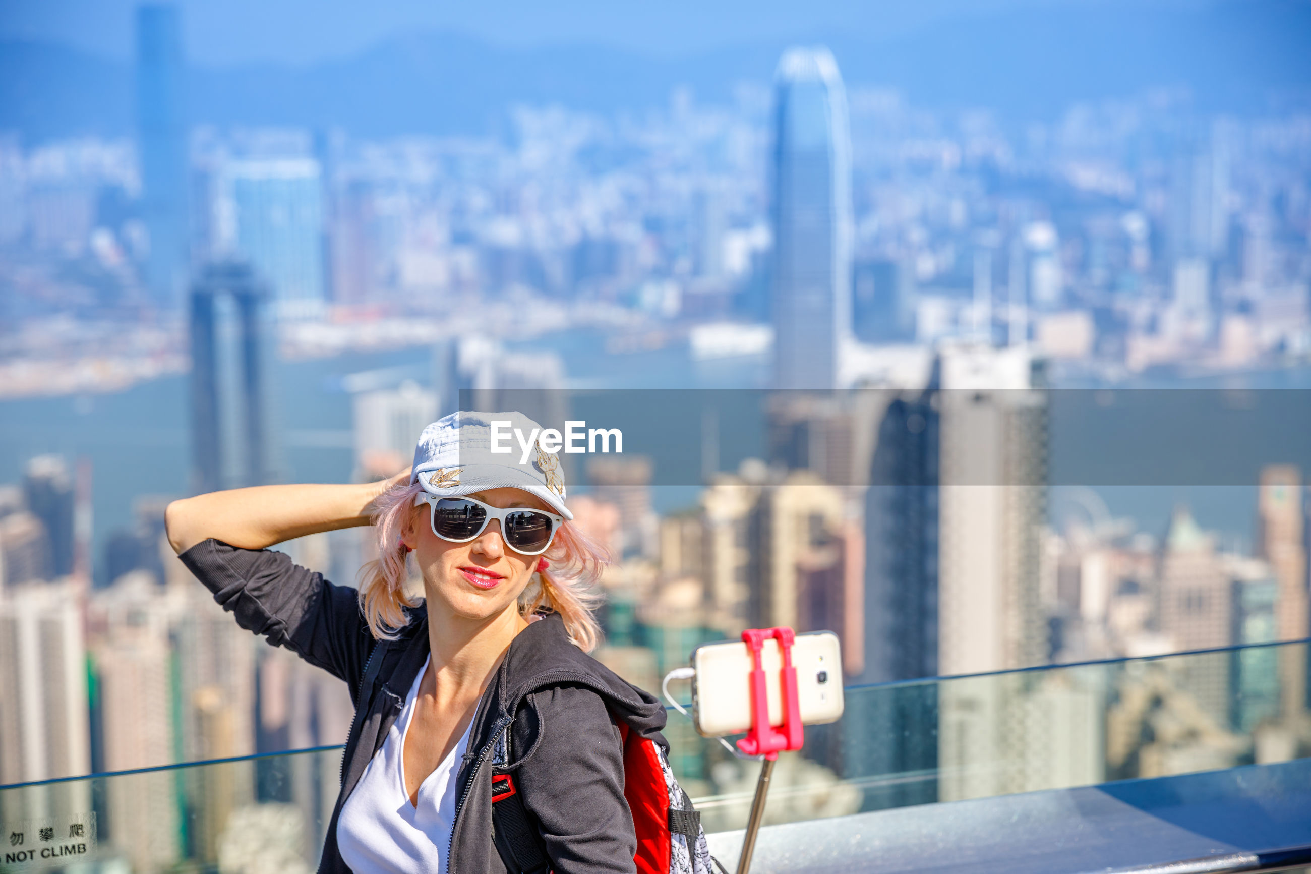 High angle view of woman taking selfie with mobile phone against cityscape