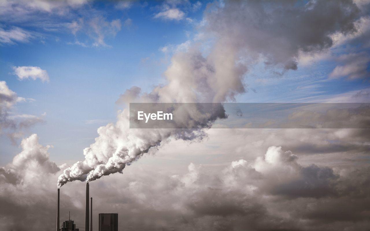 Low Angle View Of Smoke Emitting From Smokestacks Against Sky
