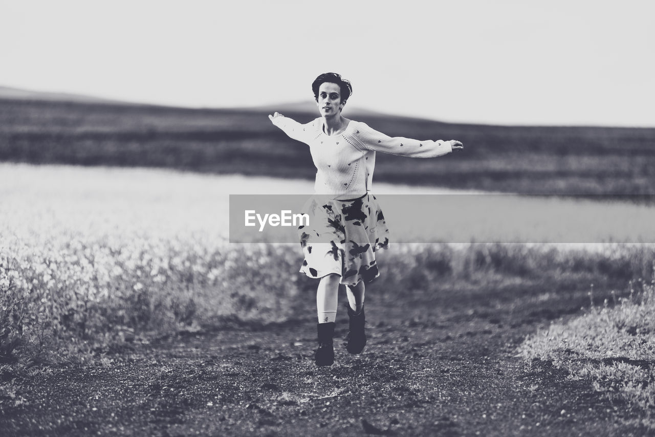 land, field, real people, front view, full length, leisure activity, lifestyles, one person, nature, arms outstretched, casual clothing, young adult, standing, human arm, day, child, happiness, smiling, limb, outdoors, arms raised