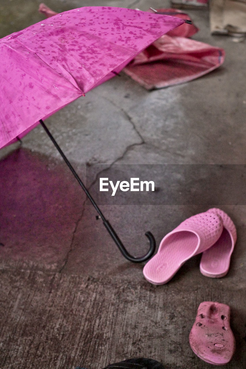 High angle view of pink slippers and umbrella