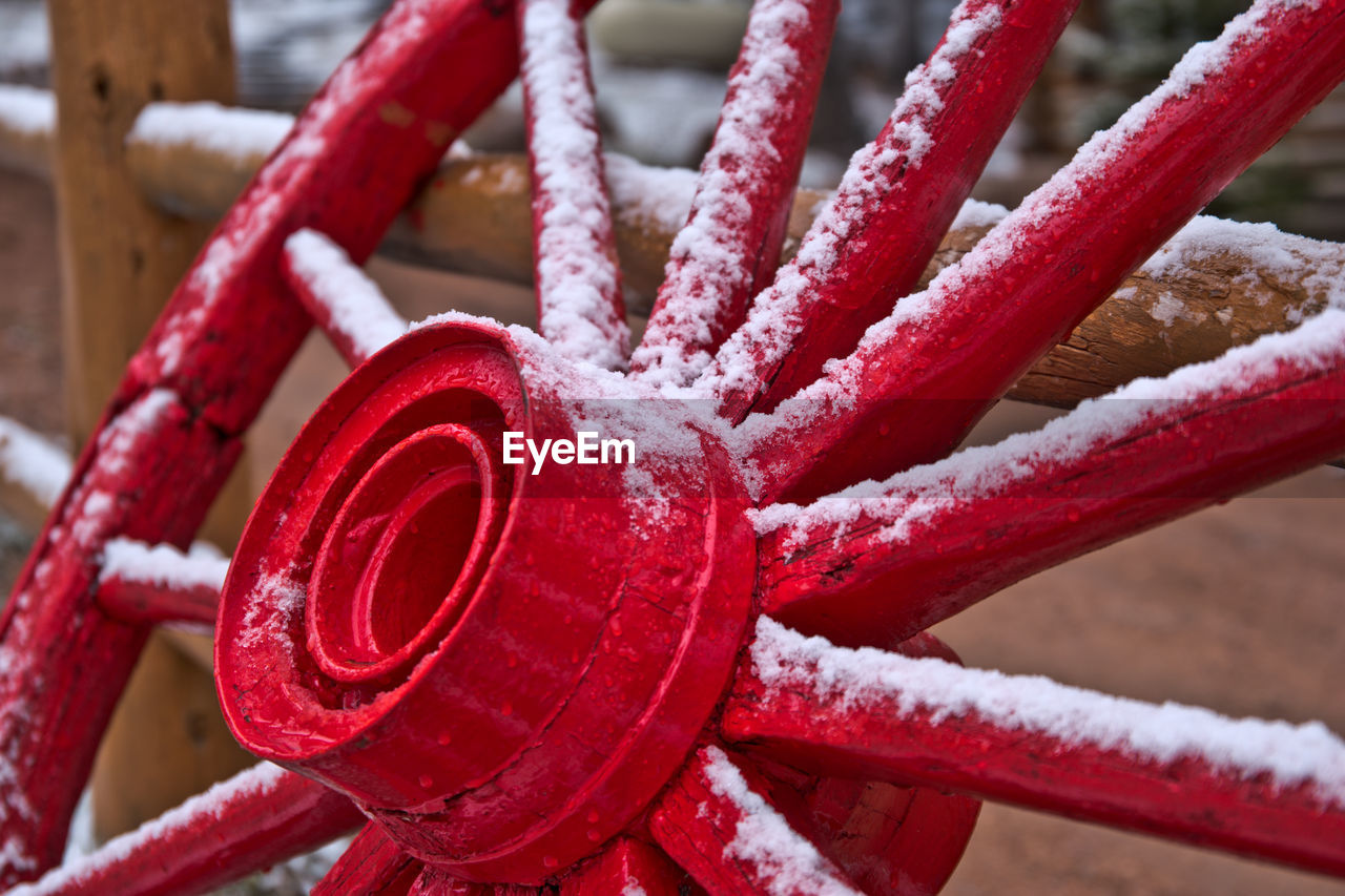 Close-Up Of Snow On Red Wagon Wheel