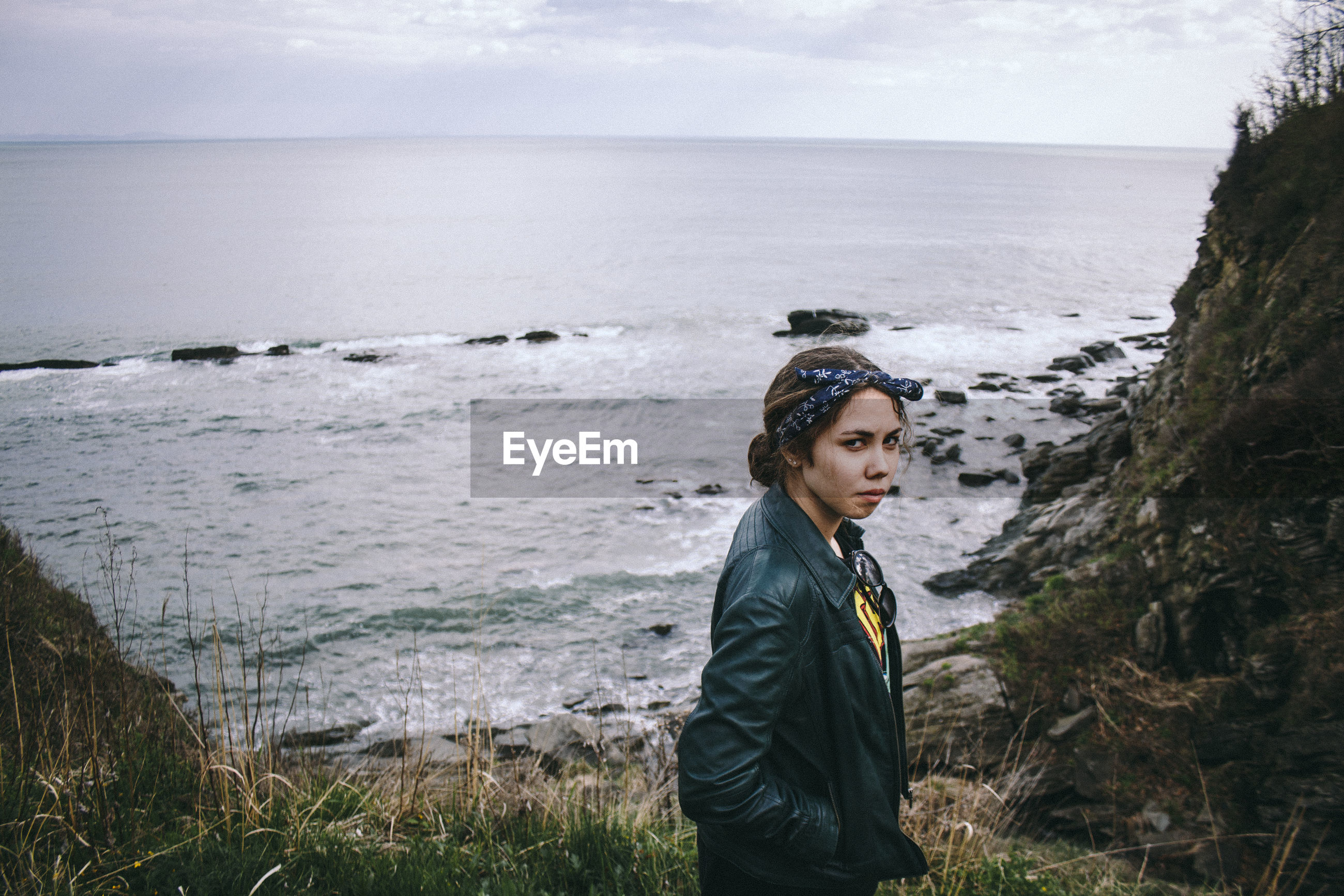 Portrait of confident woman wearing jacket standing against sea