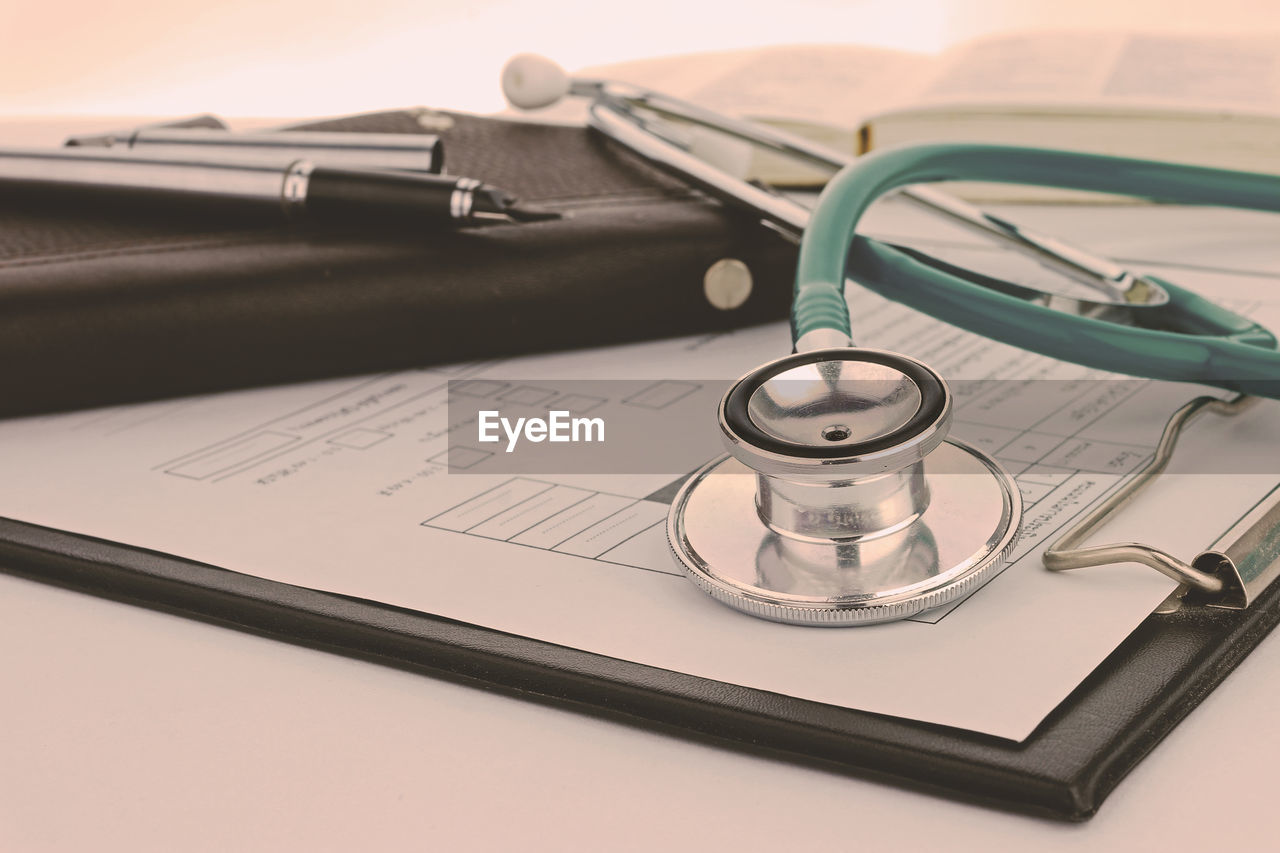 still life, stethoscope, medical equipment, medical supplies, indoors, medical instrument, table, paper, close-up, healthcare and medicine, no people, pen, medical exam, equipment, medicine, document, studio shot, book, publication, pulse trace
