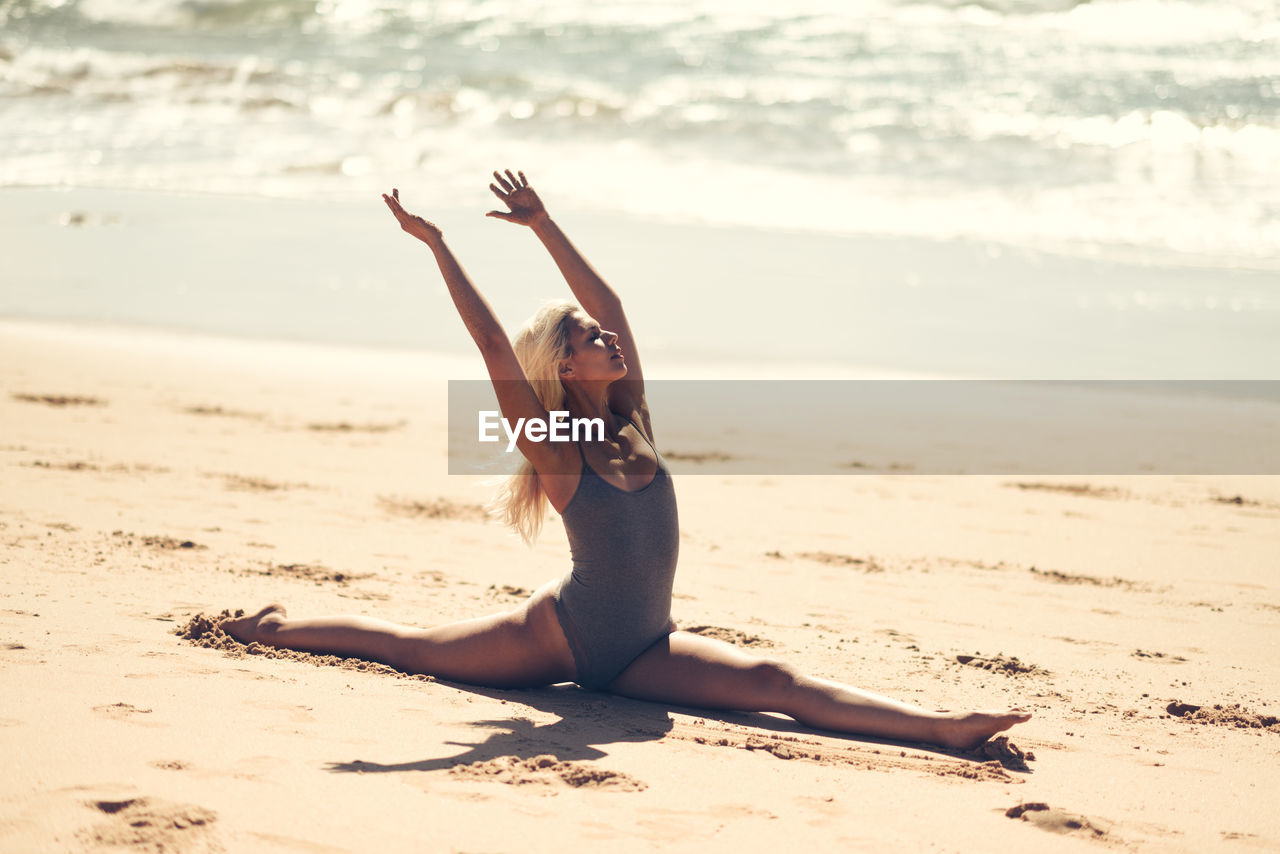 beach, land, one person, sea, leisure activity, lifestyles, human arm, sand, exercising, real people, healthy lifestyle, full length, young women, nature, arms raised, water, women, relaxation exercise, sunlight, outdoors