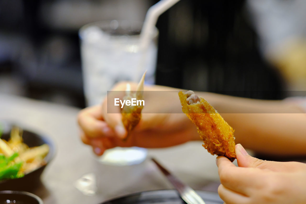 Close-up of woman holding fried chicken wing at restaurant table