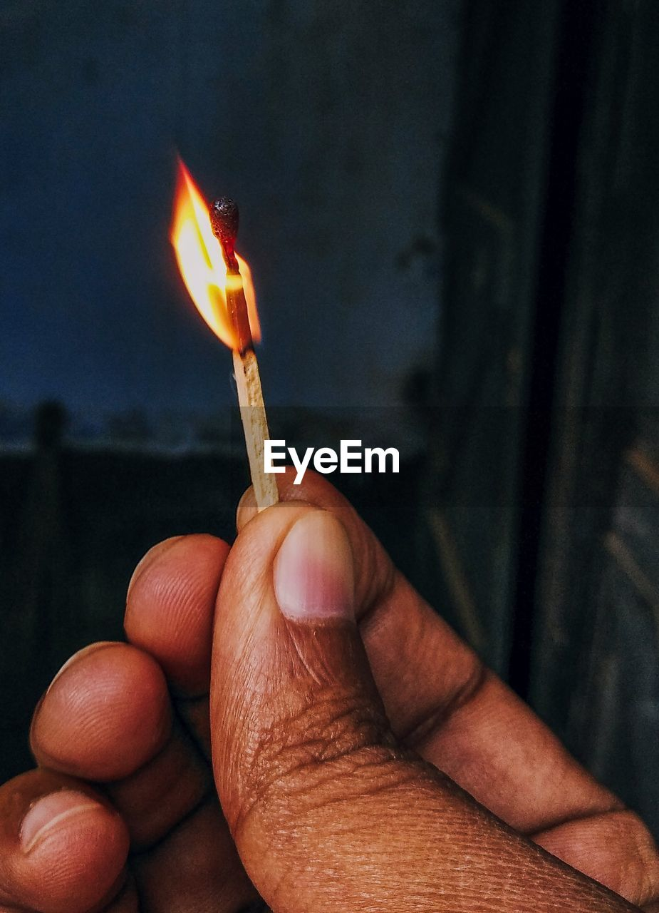 Close-up of hand holding burning candles
