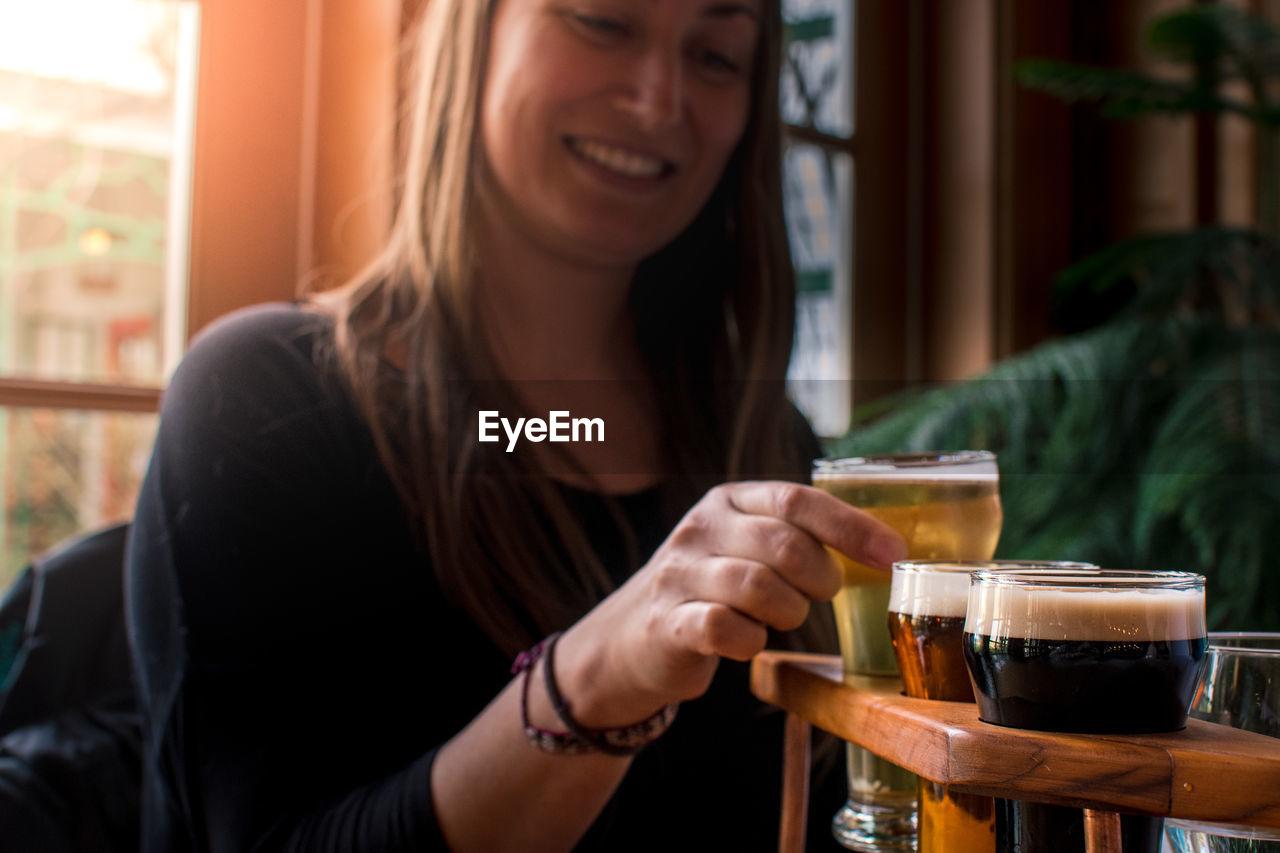 Young woman tasting craft beer at bar