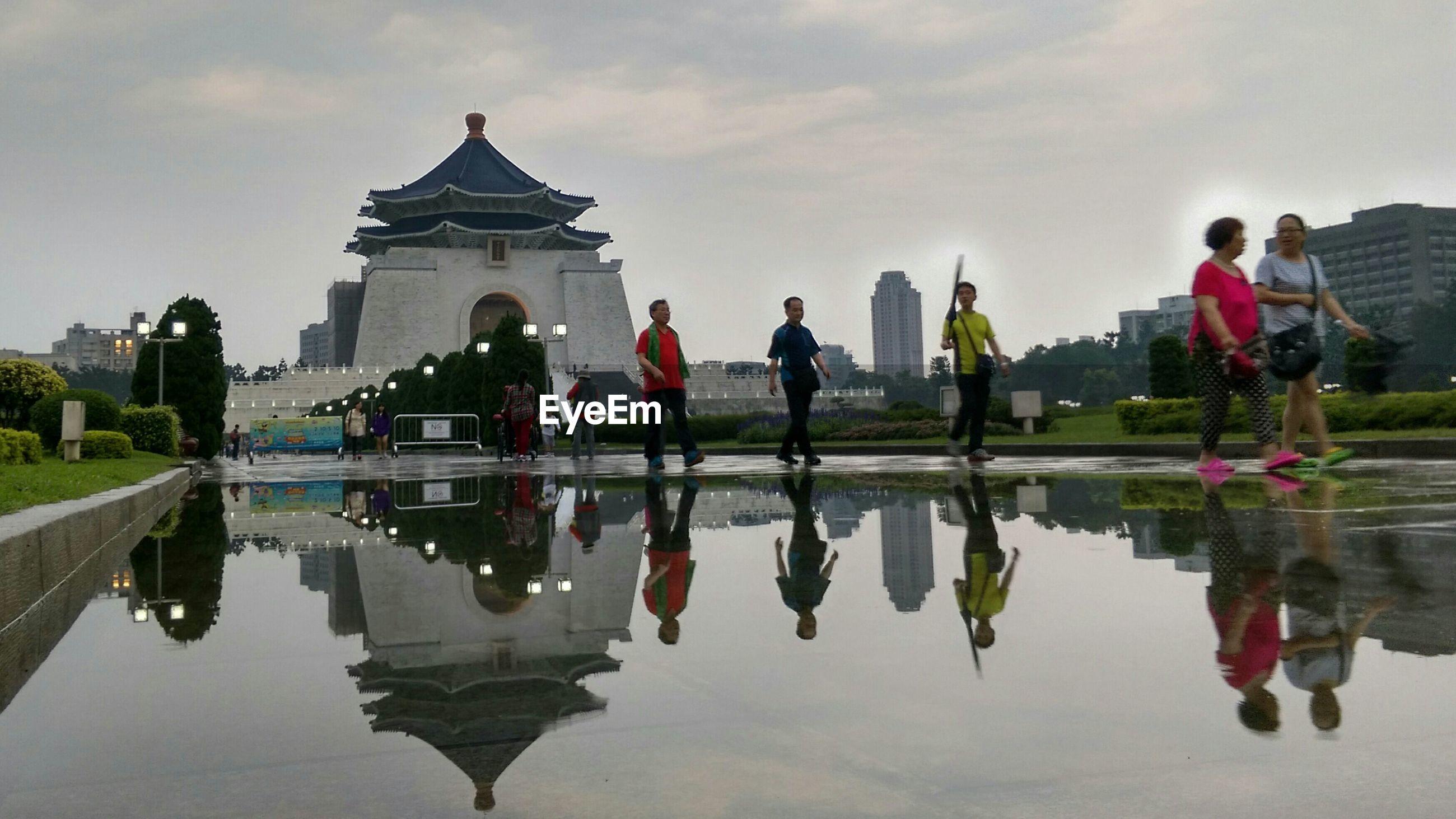 People walking by pond against chiang kai-shek memorial hall