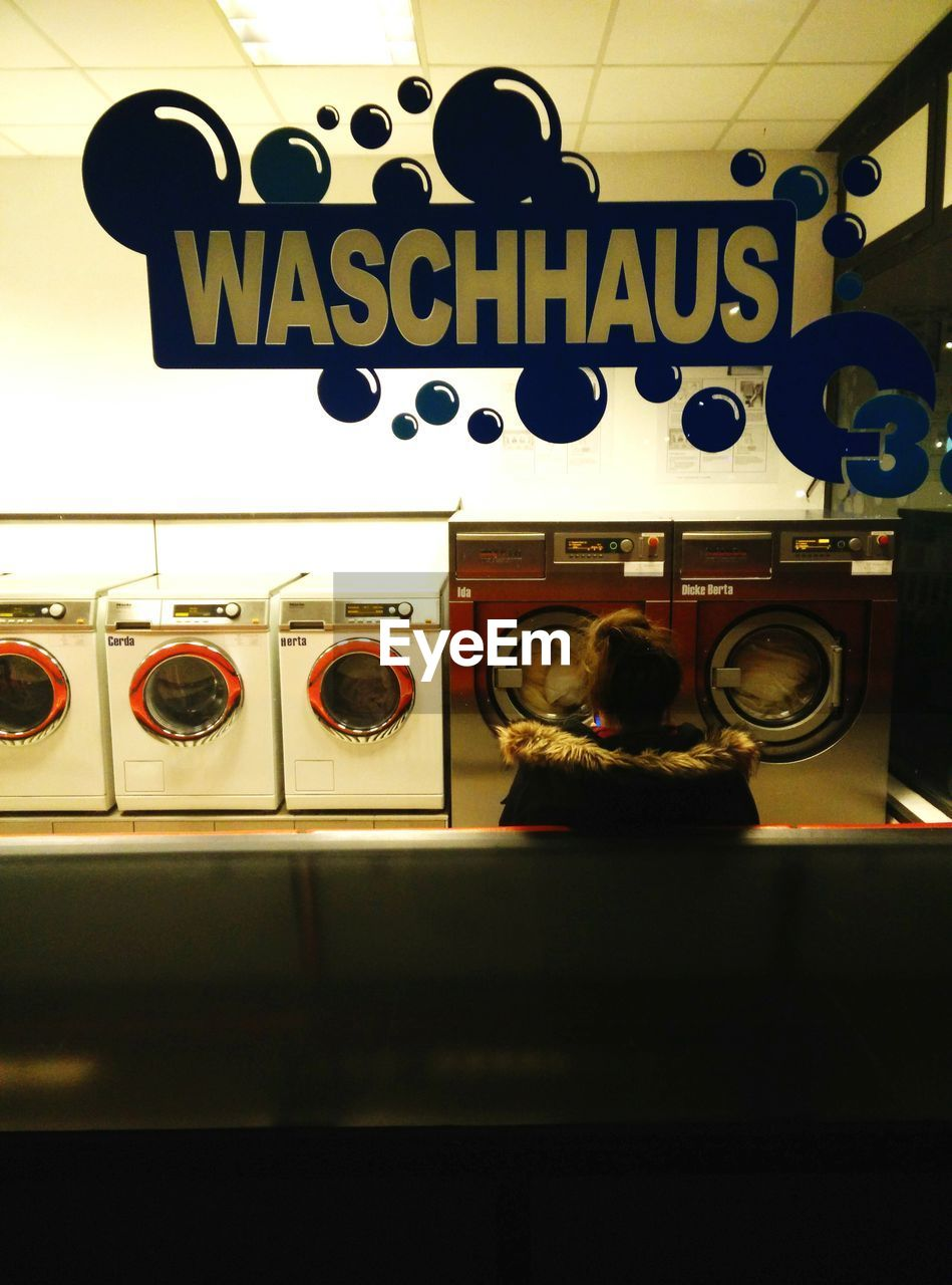 text, communication, machinery, washing machine, men, indoors, real people, one person, rear view, laundromat, leisure activity, standing, occupation, day