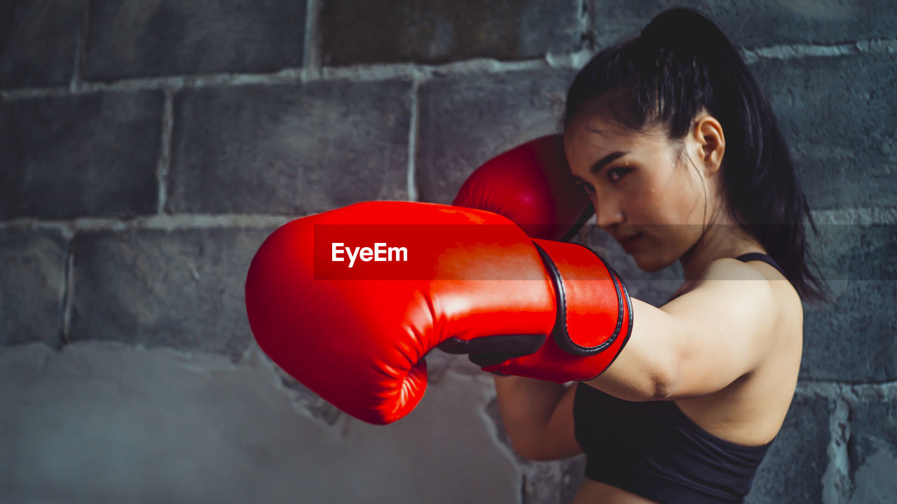 one person, boxing - sport, real people, lifestyles, red, boxing glove, sport, strength, wall - building feature, young adult, standing, young women, indoors, women, waist up, punching, sports clothing, leisure activity, hairstyle