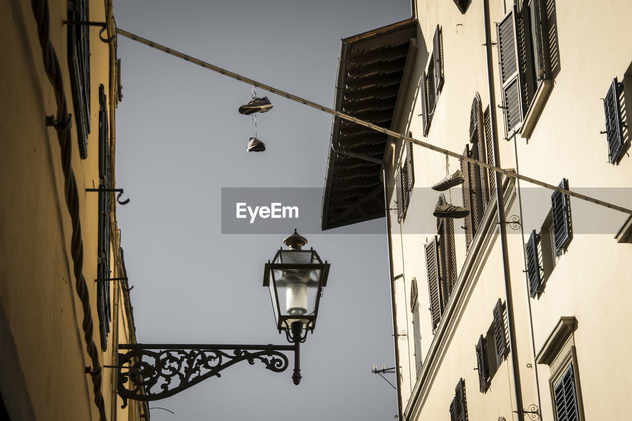 lighting equipment, architecture, built structure, low angle view, building exterior, street light, street, building, sky, no people, day, nature, hanging, electric light, outdoors, wall - building feature, electricity, electric lamp, light, clear sky, electrical equipment