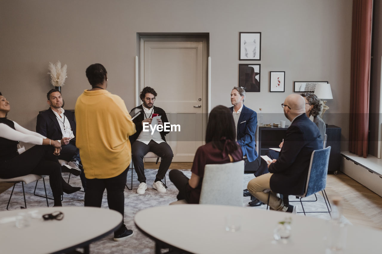 GROUP OF PEOPLE SITTING IN A ROOM
