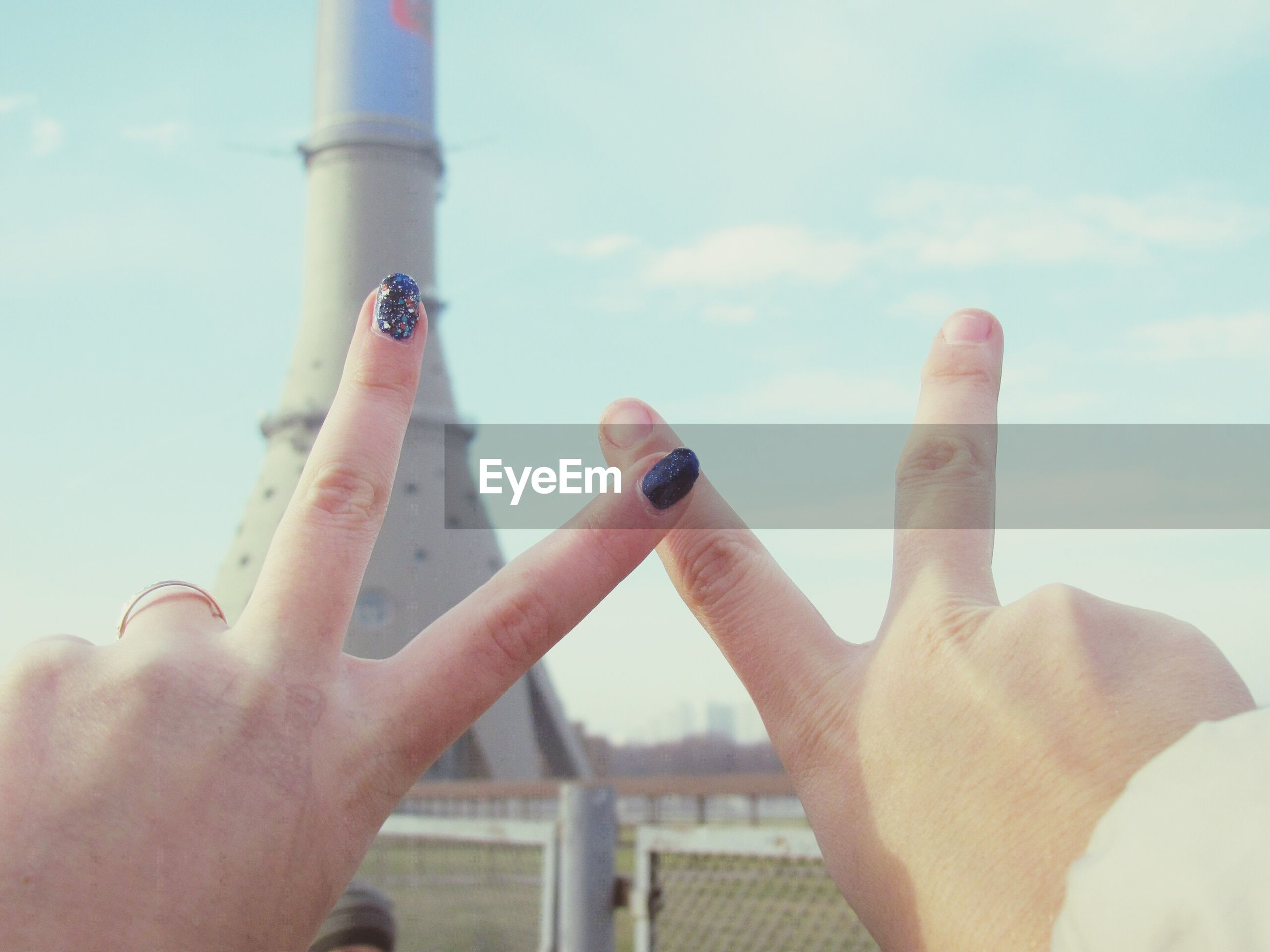 person, part of, cropped, holding, sky, human finger, personal perspective, unrecognizable person, close-up, day, leisure activity, lifestyles, built structure, outdoors, focus on foreground, architecture, cloud - sky