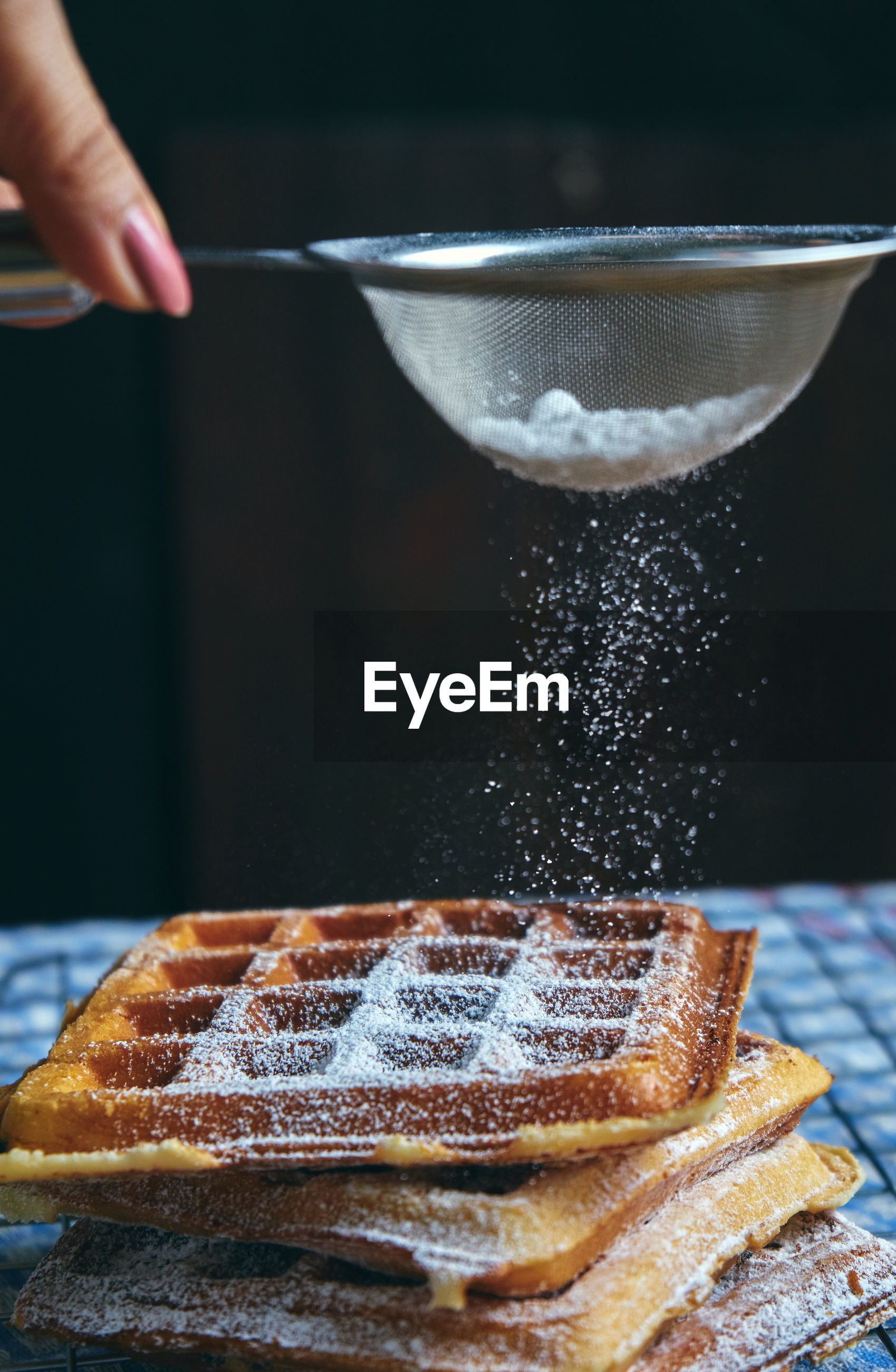 Cropped hand of woman putting powdered sugar on waffles at table