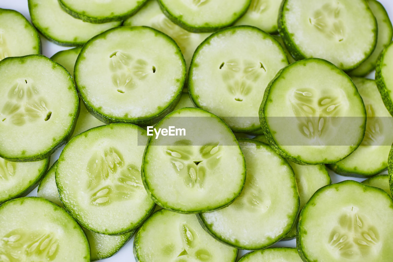 slice, food, food and drink, healthy eating, wellbeing, full frame, freshness, green color, backgrounds, cucumber, close-up, vegetable, no people, fruit, cross section, indoors, still life, large group of objects, circle, geometric shape, vegetarian food