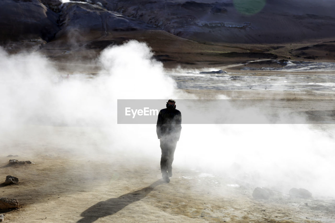 Rear View Of Man Hiking At Volcanic Landscape