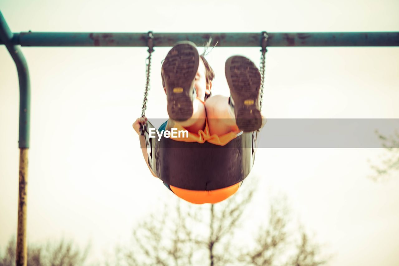 Low angle view of boy swinging against clear sky