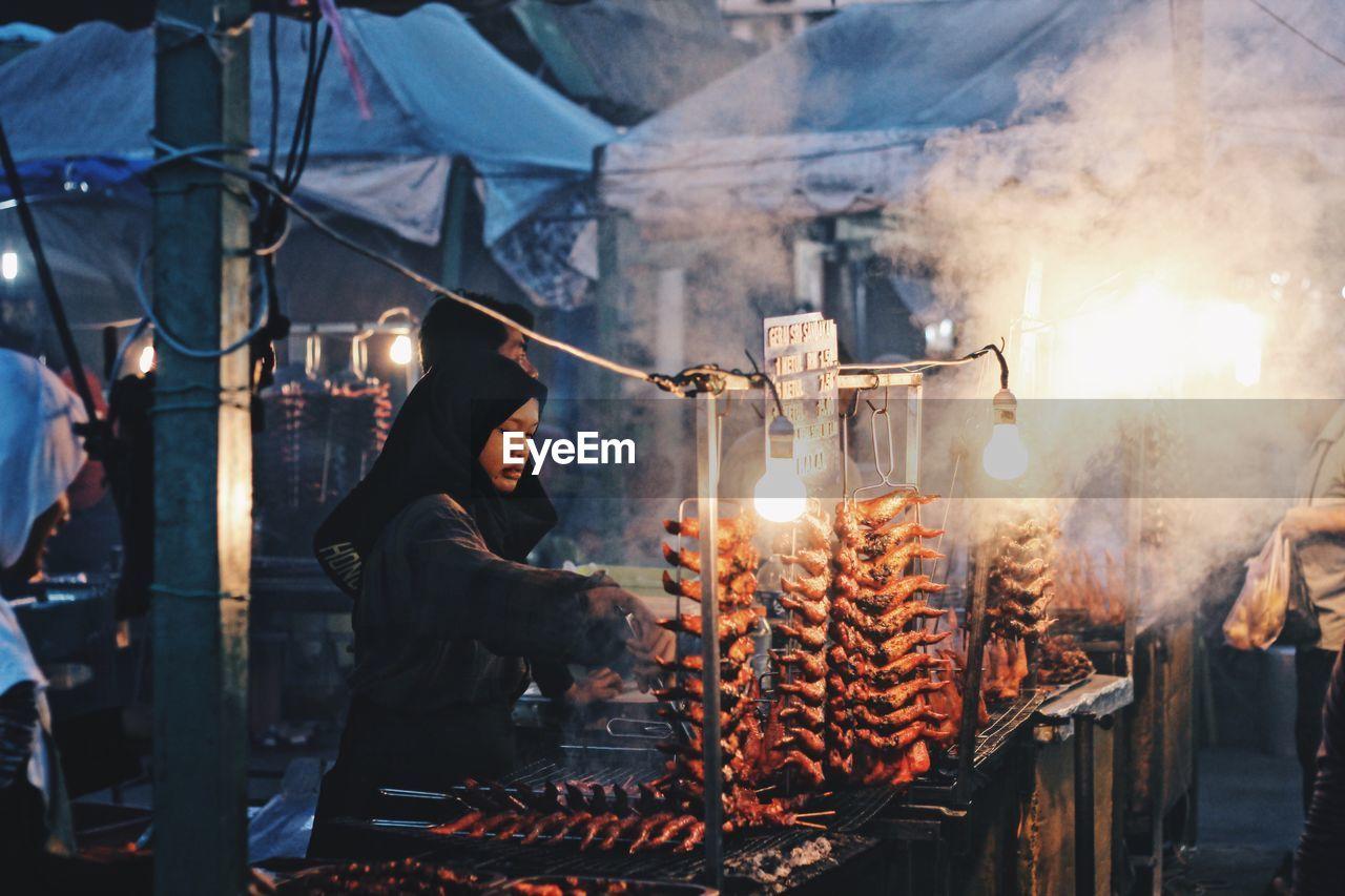Woman Preparing Food In Market Stall At Night