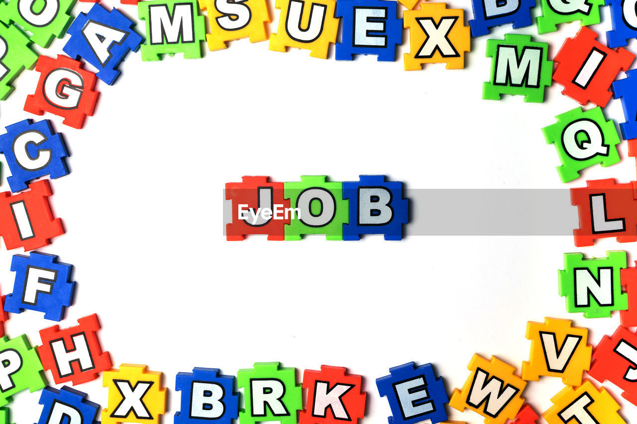 text, communication, multi colored, western script, capital letter, no people, letter, alphabet, white background, number, still life, sign, toy block, indoors, large group of objects, close-up, architecture, collection, red
