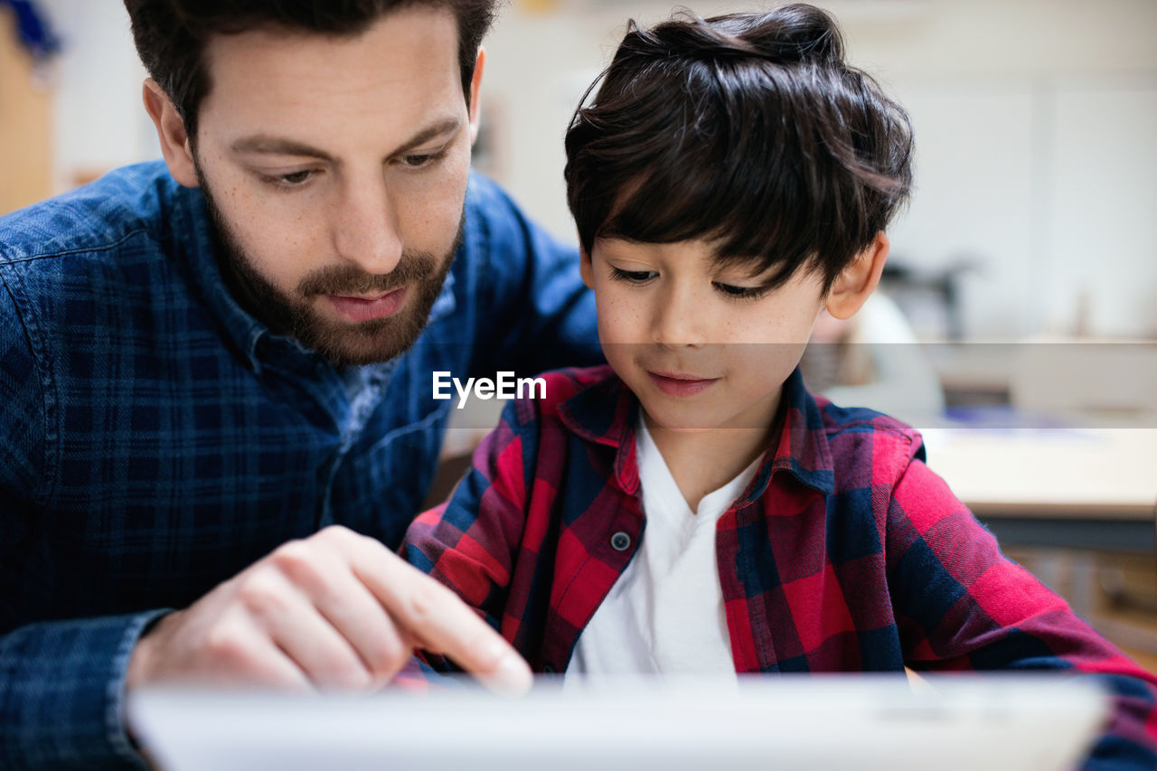 BOY LOOKING AT CAMERA WHILE SITTING ON LAPTOP
