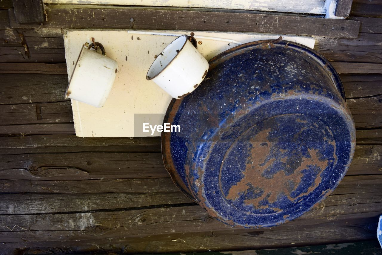 Close-Up Of Old Bowl And Cups Hanging On Wooden Wall