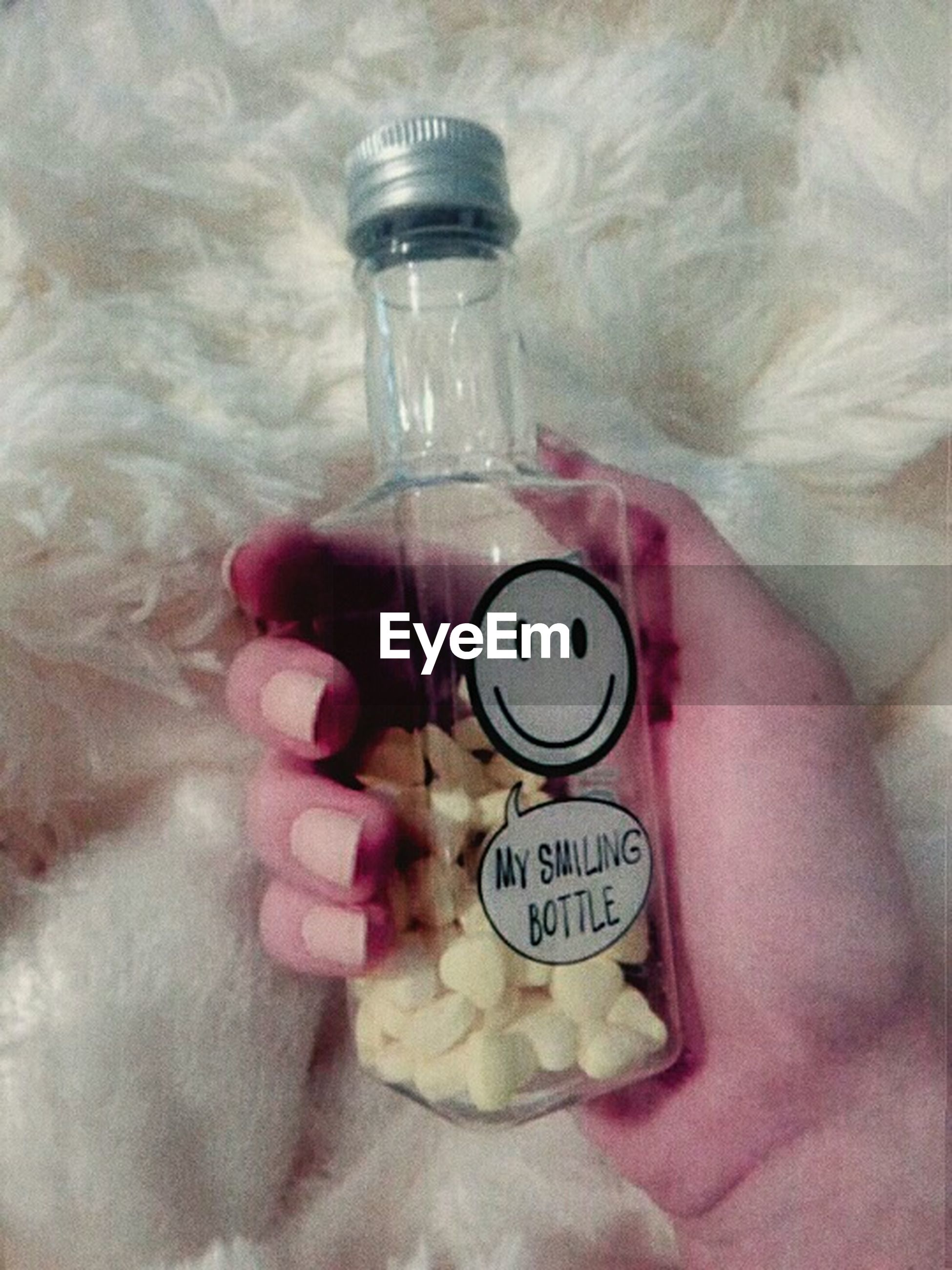 container, human hand, indoors, bottle, holding, close-up, hand, glass - material, jar, real people, pink color, one person, text, human body part, transparent, table, communication, food and drink, message