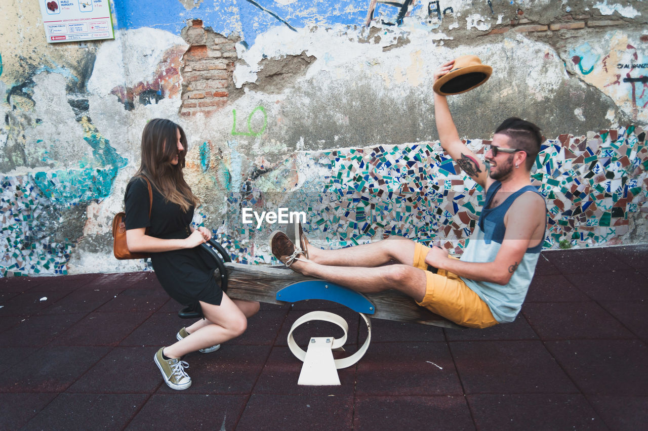 Happy Friends Playing Seesaw Against Damaged Wall