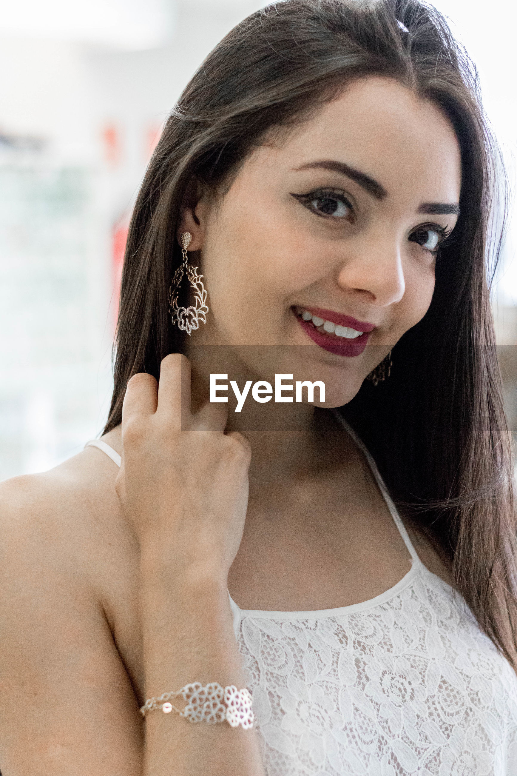 Portrait of smiling young woman trying earring while standing in store