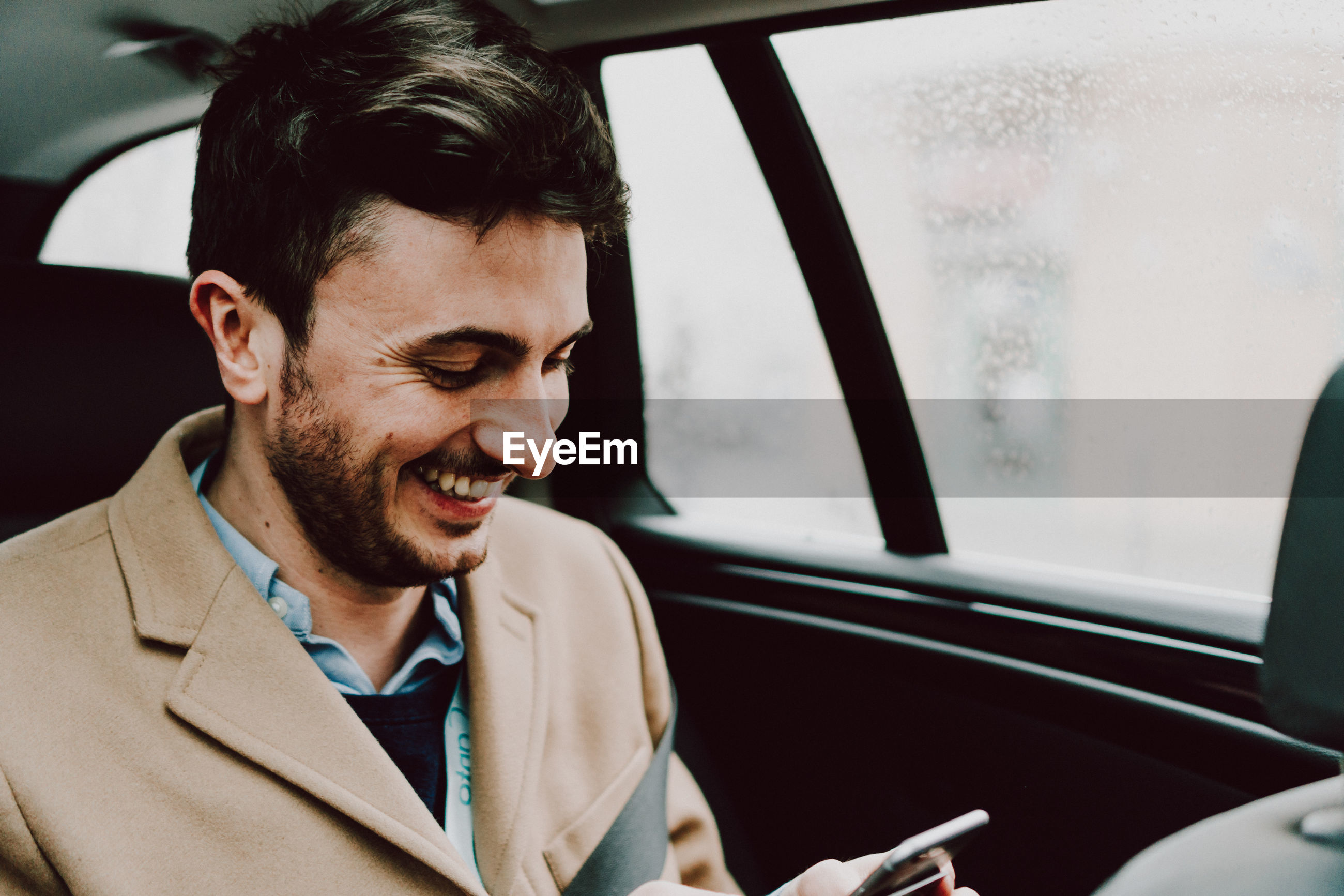 Close-up of happy businessman using phone while traveling in car
